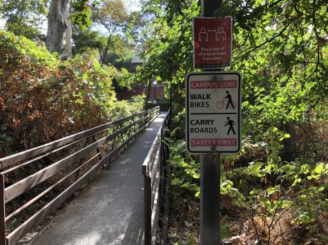 A bridge with a sign displaying the campus rules regarding bikes and boards.