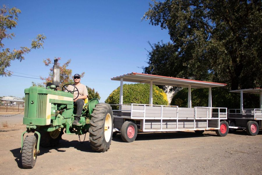Tour guide Hunter Ortiz awaits visitors as he checks the vintage tractor for wear, taken on Oct. 15, 2021.